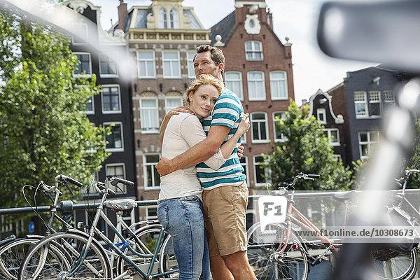 Niederlande  Amsterdam  Paar in der Stadt umarmend