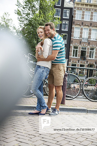 Niederlande  Amsterdam  glückliches Paar  das sich in der Stadt umarmt