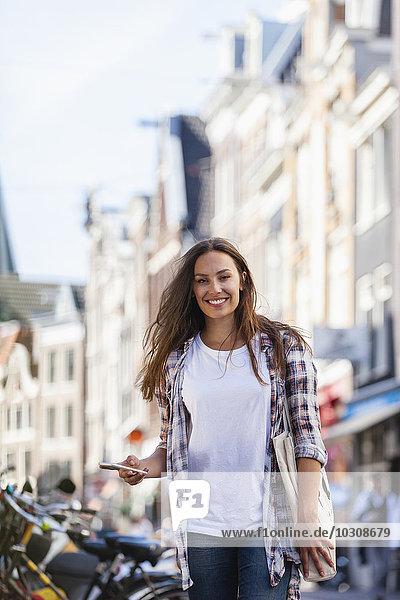 Niederlande  Amsterdam  lächelnde junge Frau in der Stadt mit Handy