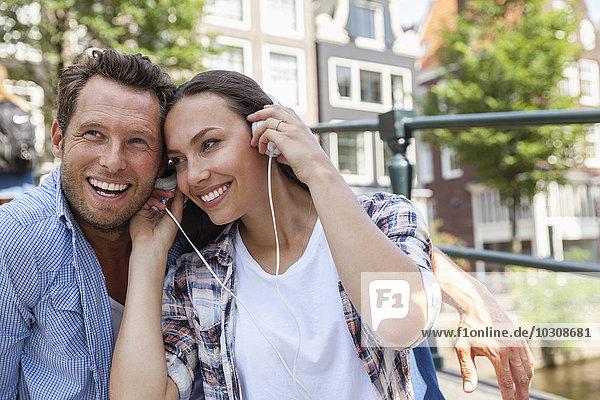 Niederlande  Amsterdam  happy couple sharring Kopfhörer im Freien