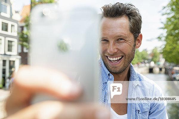 Niederlande  Amsterdam  glücklicher Mann  der einen Selfie am Stadtkanal nimmt.