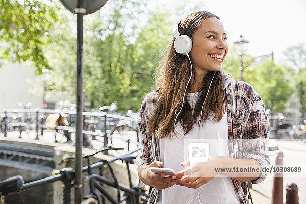 Niederlande  Amsterdam  glückliche junge Frau mit Kopfhörer