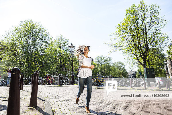 Niederlande  Amsterdam  glückliche junge Frau  die von einer Brücke rennt