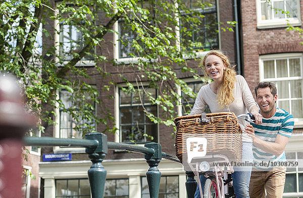 Niederlande  Amsterdam  glückliches Paar mit Fahrrad in der Stadt