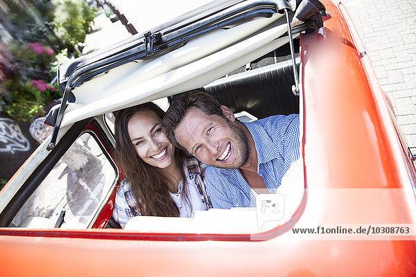Glückliches Paar schaut durch das offene Schiebedach eines Kleinwagens