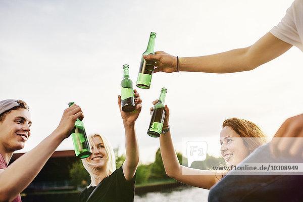 Freunde trinken zusammen Bier am Wasser.