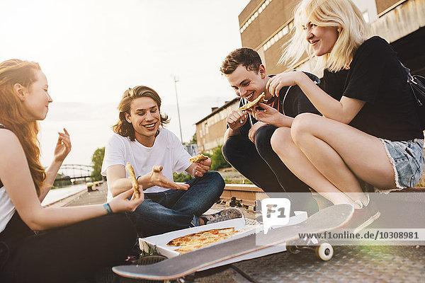 Freunde sitzen zusammen im Freien und teilen sich eine Pizza.