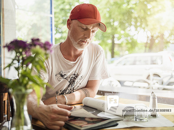 Germany  Berlin  Mature man sitting in cafe  reading magazines