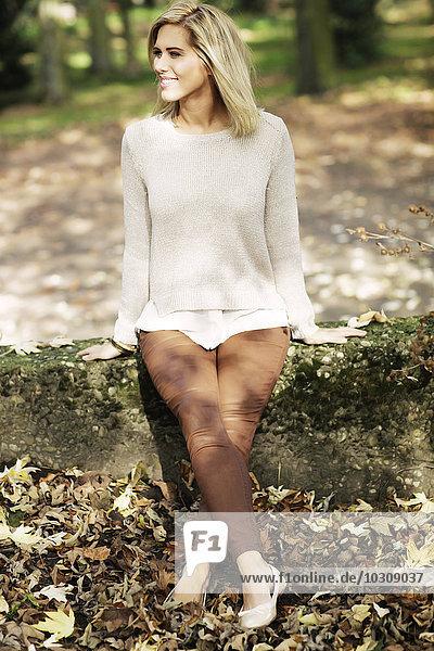 Lächelnde blonde Frau in Strickpullover an der Wand sitzend