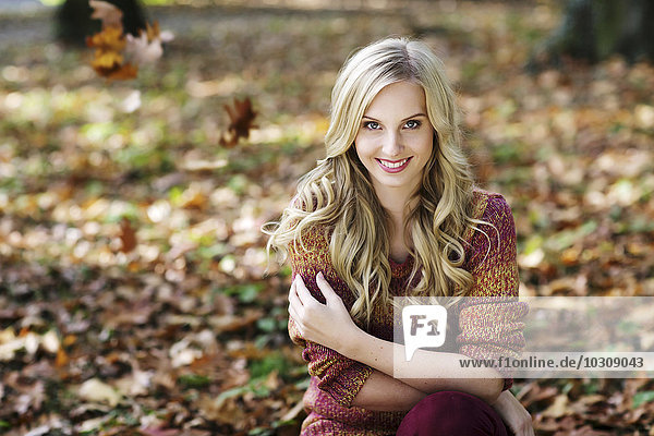 Portrait of smiling blond woman wearing knit pullover sitting in autumnal forest