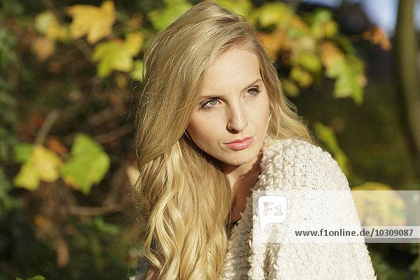 Porträt einer blonden Frau vor Herbstblättern