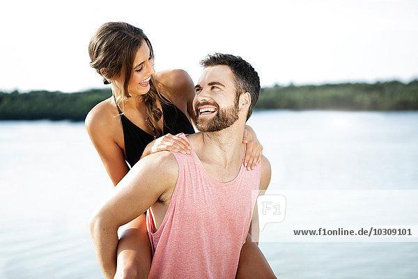 Deutschland  Haltern  Mann gibt seiner Freundin ein Huckepack vor dem Silbersee