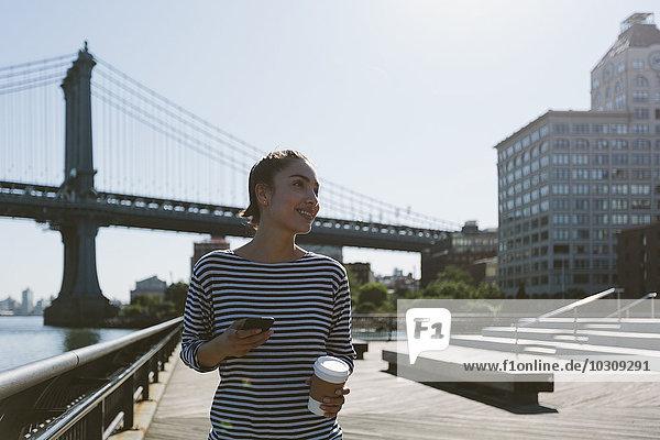 USA,  New York City,  Portrait der jungen Frau mit Smartphone und Kaffee zum Mitnehmen