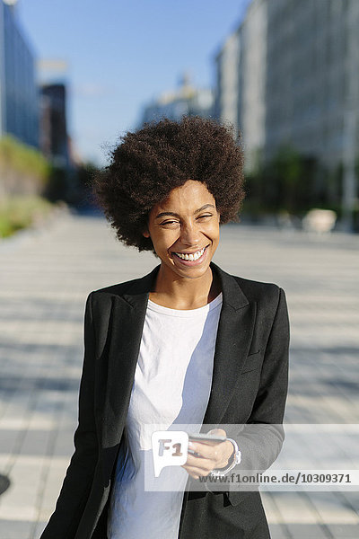 USA  New York City  portrait of smiling businesswoman with smartphone