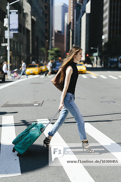 USA  New York City  junge Frau mit Rollkoffer überquert eine Straße