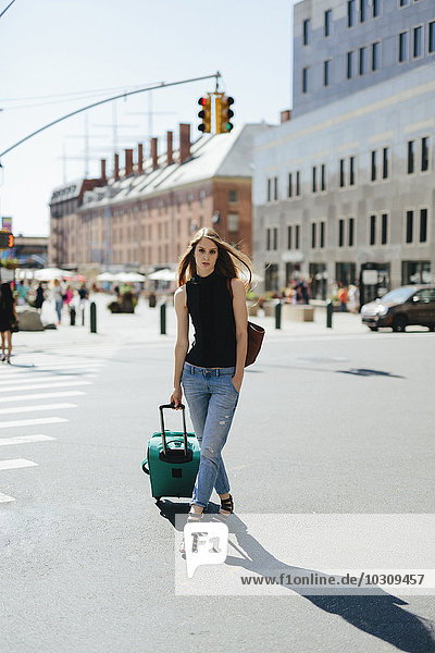 USA  New York City  young woman with rolling suitcase standing on a street
