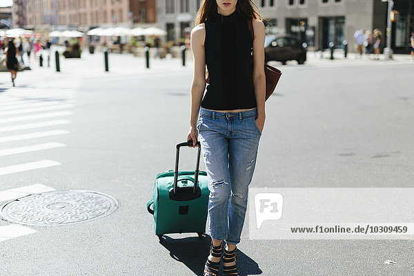 USA  New York City  junge Frau mit Rollkoffer auf der Straße stehend