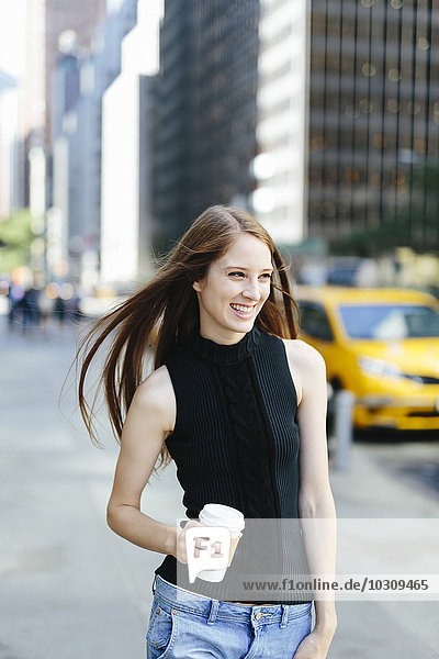 USA  New York City  portrait of laughing young woman with coffee to go