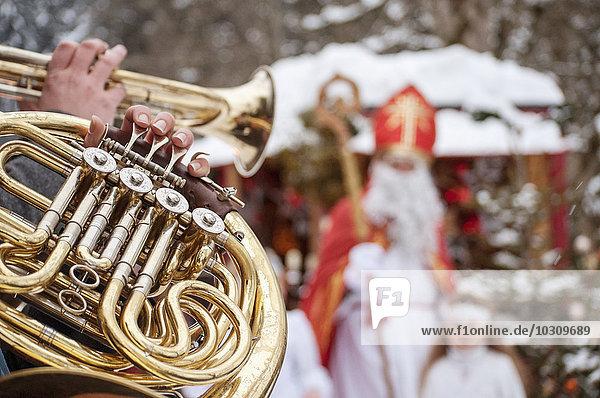 Musiker spielt Horn mit Engel und Weihnachtsmann im Hintergrund