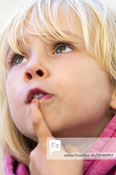 Portrait of little girl with finger on mouth