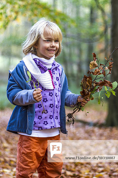 Portrait of little girl with autumn foliage and plants