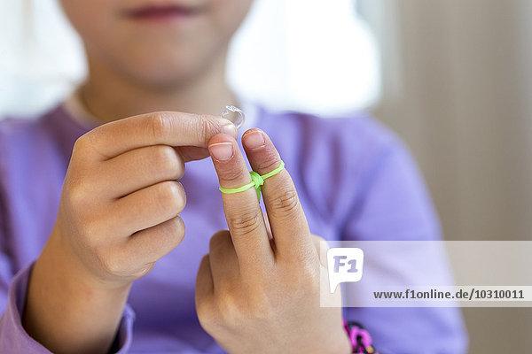 Fingers of little girl making loom bracelets