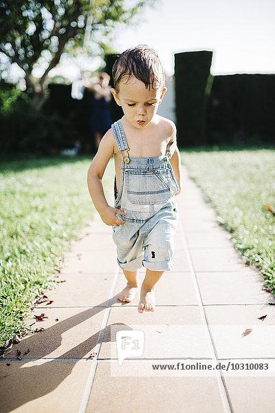 Kleiner Junge läuft barfuß auf Bodenplatten im Garten Kleiner Junge läuft barfuß auf Bodenplatten im Garten