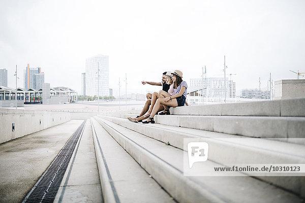 Spanien  Barcelona  Drei glückliche Freunde sitzen auf der Treppe