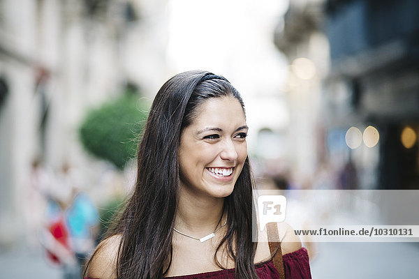 Portrait of a smiling young woman in the city