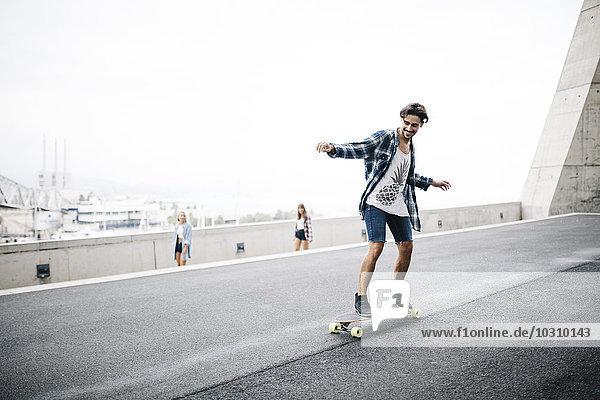 Junger Mann balanciert auf Longboard  Mädchen schauen zu