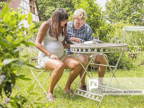 Junges Paar  das ein Baby erwartet  sitzt im Garten und liest. Junges Paar, das ein Baby erwartet, sitzt im Garten und liest.