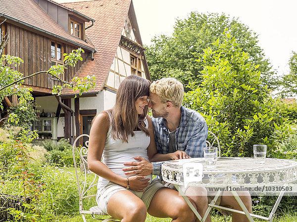 Junges Paar erwartet Baby  sitzt im Garten  Mann berührt Bauch der Frau