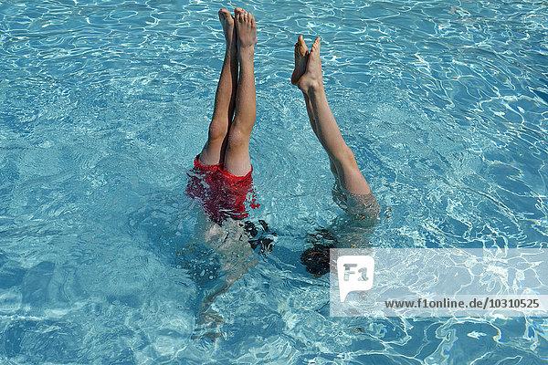 Teenager Junge und Mädchen beim Handstand im Schwimmbad