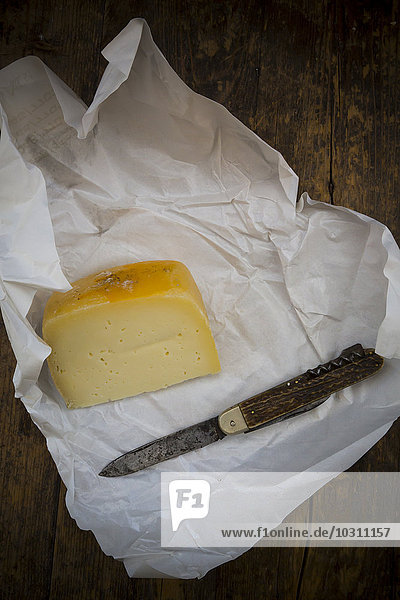 Ein Stück Caciotta Monte Baldo und ein Taschenmesser auf Pergamentpapier und dunklem Holz. Ein Stück Caciotta Monte Baldo und ein Taschenmesser auf Pergamentpapier und dunklem Holz.