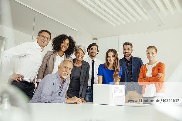 Portrait von lächelnden Geschäftsleuten mit Laptop im Konferenzraum