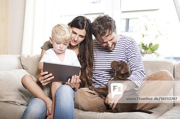 Eltern  kleiner Sohn und ihr Hund sitzen zusammen auf der Couch.
