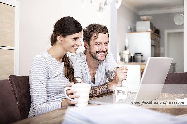 Lächelndes Paar sitzt am Holztisch und schaut auf den Laptop.