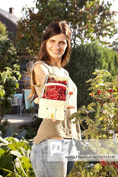 Lächelnde Frau mit roten Johannisbeeren im Korb