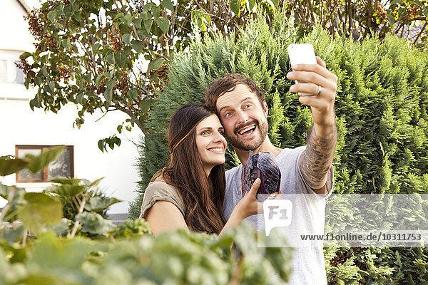 Pärchen mit einem Selfie im Garten mit Rotkohl