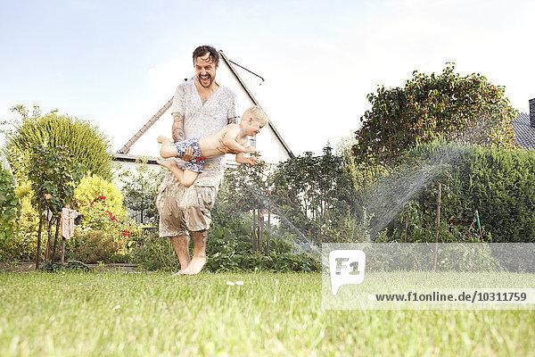 Vater und sein kleiner Sohn beim gemeinsamen Spaß im Garten