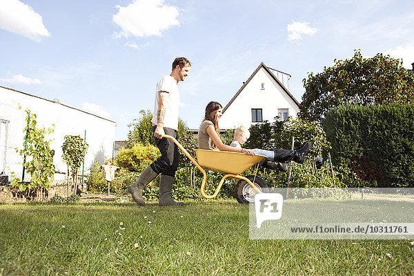 Mann schiebt Schubkarre mit Mutter und seinem kleinen Sohn durch den Garten