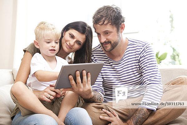 Eltern und kleiner Sohn sitzen auf der Couch mit digitalem Tablett