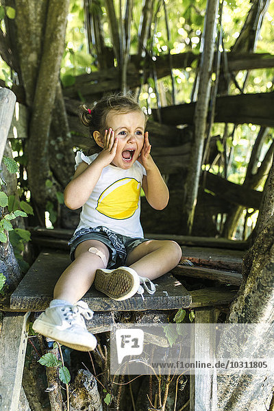Portrait of screaming little girl sitting in the garden