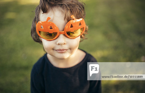 Porträt eines kleinen Mädchens mit Halloween-Brille in Kürbisform