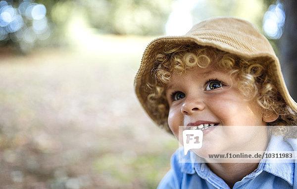 Porträt eines lächelnden blonden Jungen mit Hut Porträt eines lächelnden blonden Jungen mit Hut
