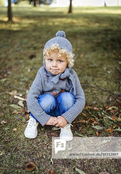 Porträt eines kleinen Jungen  der auf einer Wiese hockt.