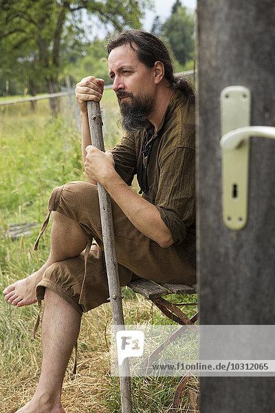 Mann sitzend mit Wanderstock an der Holzhütte