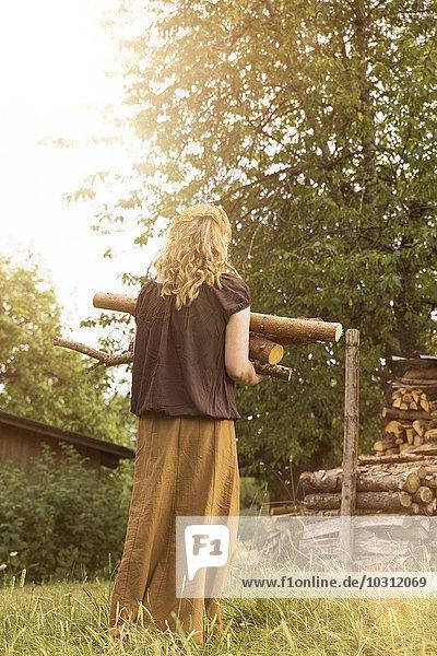 Frau trägt Brennholzstapel