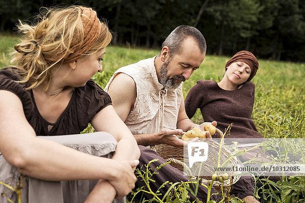 Drei Personen sitzen auf dem Feld mit Kartoffeln im Weidenkorb