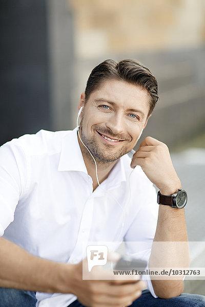 Porträt eines lächelnden Mannes mit MP3-Player und Kopfhörer